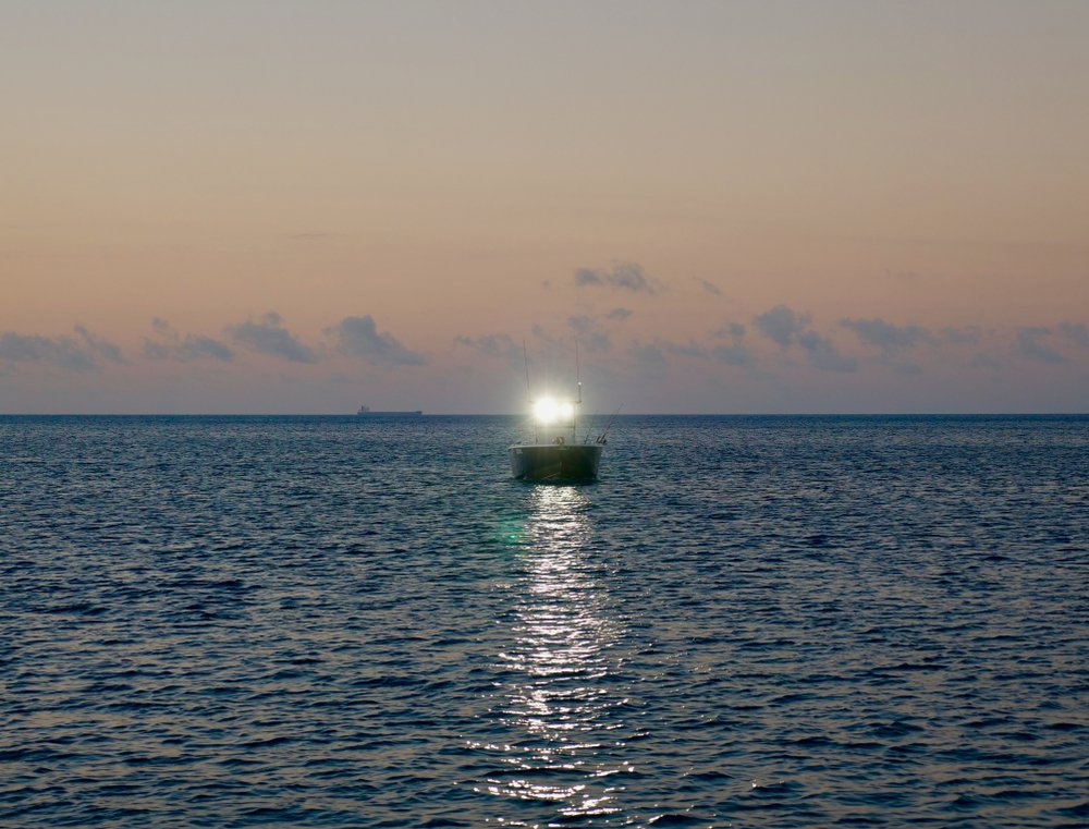 When boating at night, what does a single white light on a boat tell you